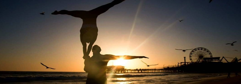Couple doing a yoga pose along the beautiful Santa Monica Pier in LA during sunset.