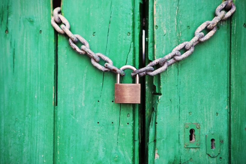 A sturdy lock of a bright green door.